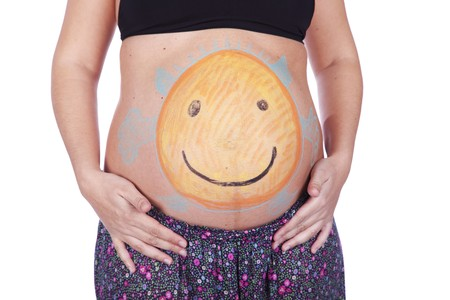 Pregnant woman with a painted belly of a happy and smiling little devil Stock Photo - 7812134
