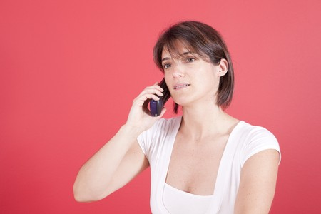 woman talking on the telephone next to a red wall photo