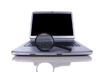 Laptop with a magnify glass to search online information (isolated on white) photo