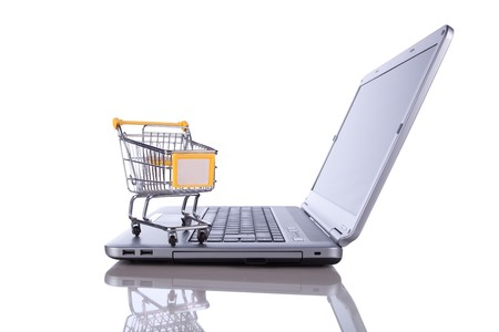 buying online: shopping cart over a laptop isolated on white with reflection