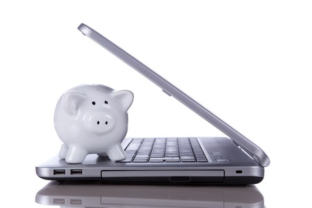 Piggy bank over a modern laptop, the cost of technology and information (isolated on white) Stock Photo - 7810321