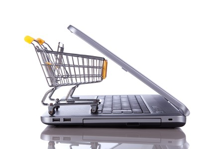 shopping cart over a laptop isolated on white with reflection Stock Photo - 7810599