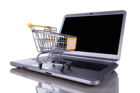shopping-cart over a laptop isolated on white with reflection photo