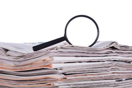 investigate: Magnify glass over a stack of newspaper to find fresh information (isolated on white) Stock Photo