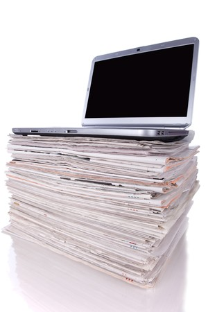 Laptop over a stack of newspapers for internet information access (isolated on white) photo