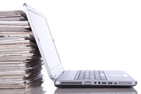 stack of newspaper next to a laptop (isolated on white) Stock Photo - 7810709