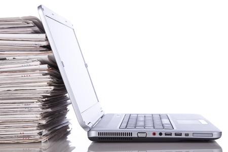 newspapers: stack van krant naast een laptop (geïsoleerd op wit)