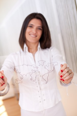 Happy businesswoman at her office showing a world map schema (selective focus with shallow DOF). photo