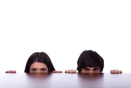 looking around: two business person hiding and peeking behind the office desk