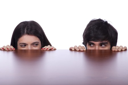 two business person hiding and peeking behind the office desk photo