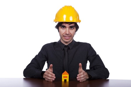 young construction engineer protecting a small yellow house photo