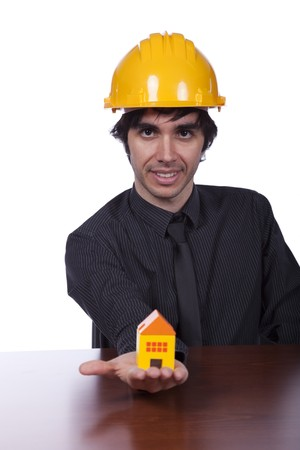 young construction engineer showing you a small yellow house photo