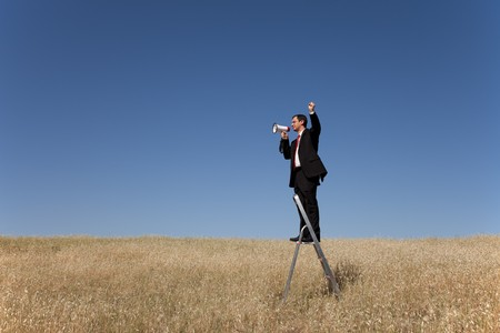 businessman in the field speaking to nobody photo