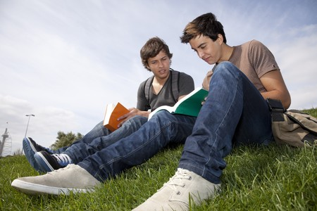two young student reading books at the school park photo