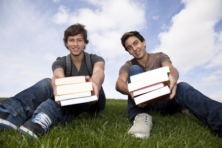two young students giving you books photo