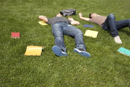 two young student lying down at the school grass after long hours of study photo