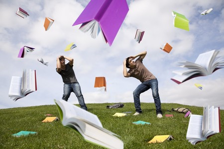 panicking: Teenager students outside protecting there heads from a rain of books