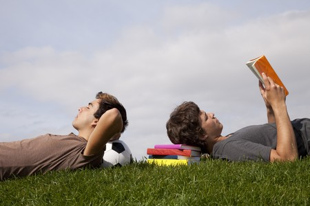 two young students sleeping at the grass over books and a soccer ball photo