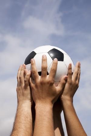 gevangen: Voet bal team een bal naar de hemel te verhogen Stockfoto