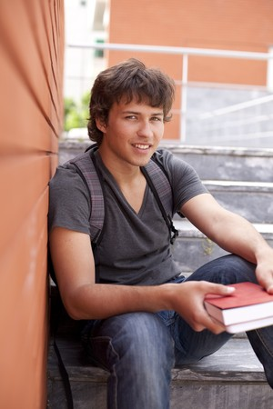 handsome teenager next to a red brick wall (selective focus) photo