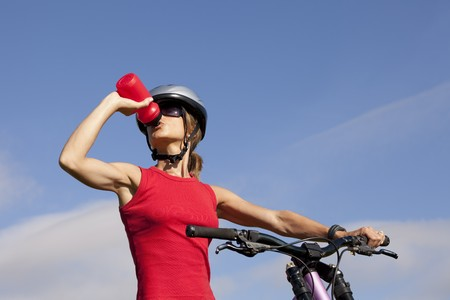 blue helmet: Biker woman refreshing drinking water at her morning exercise Stock Photo