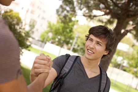 gratitudine: Felice giovane studente, dare una stretta di mano al suo compagno di classe (fuoco)