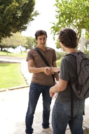 Happy young student giving a handshake to his classmate (selective focus) Stock Photo - 7812127