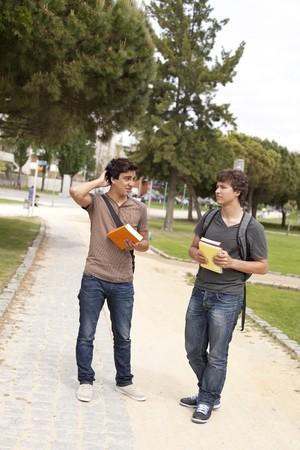 dos personas hablando: dos joven estudiante hablando en el Parque de la escuela