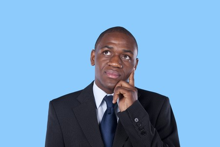 African businessman thinking with a blue background photo