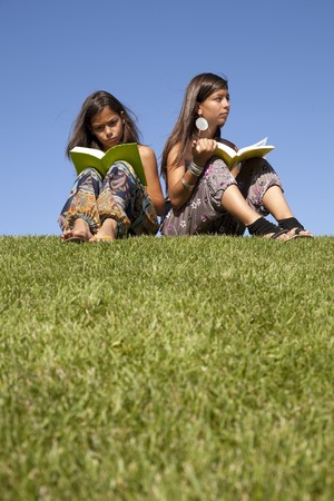 two young sisters reading books at the park photo
