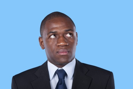 African businessman looking up to the copyspace (blue background) Stock Photo - 7810843