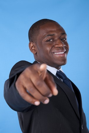 Happy african businessman pointing to you with a blue background photo