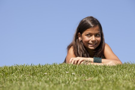 young child laying on the grass in a summer day photo