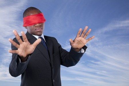 disoriented: Hostage african businessman with a red blindfold covering his eyes