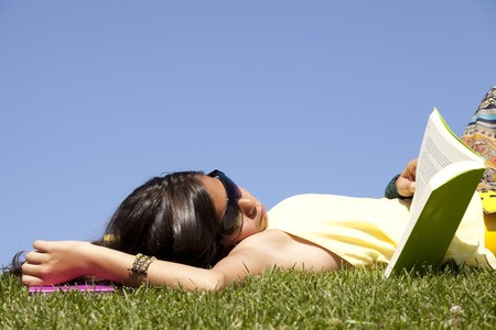 little girl relaxing at the top of the field reading a book photo