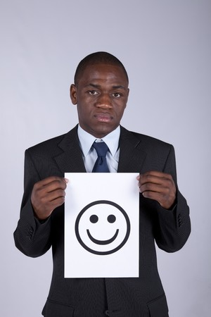 serious african businessman holding a smile symbol printed on a paper photo