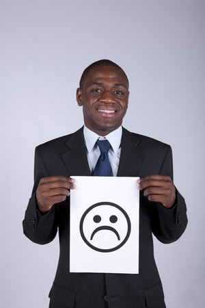 untrustworthy: happy african businessman holding a sad smile symbol printed on a paper Stock Photo