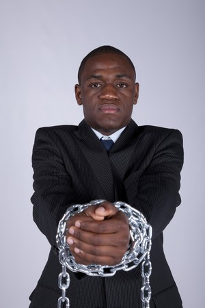 of african descent: Arrested african businessman with a steel chain in his hands