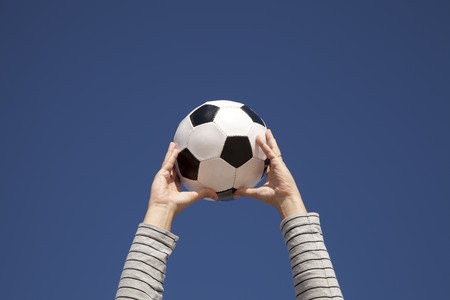 Hands holding a soccer ball up to the sky photo