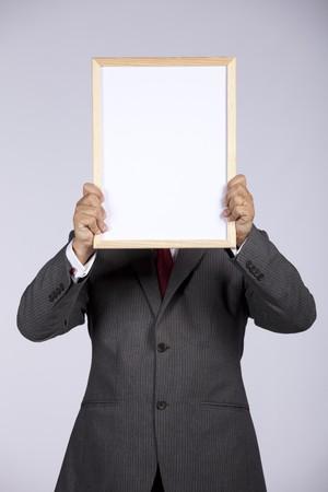 businessman holding a blank whiteboard photo