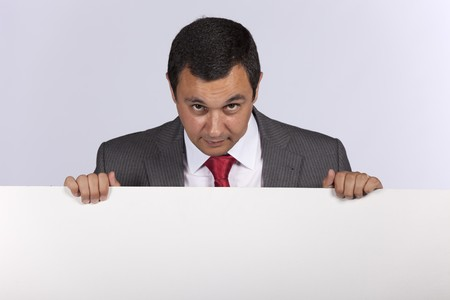 Businessman holding a blank billboard and looking to the camera photo