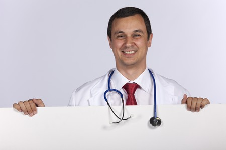 friendly male doctor holding a banner (isolated on white) photo