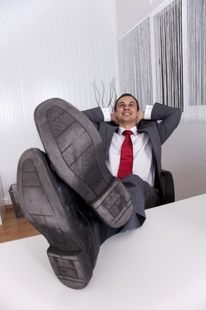 businessman relaxing at the office with his shoes on the desk (isolated on white) photo