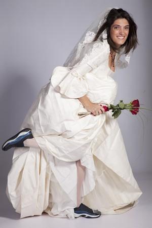 Beautiful bride ready to run away (grey background) Stock Photo - 7810738