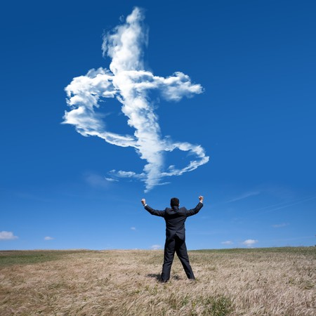 businessman showing his success at the field looking to a cloud with a dollar shape photo