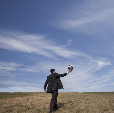 Businessman holding a soccer ball up in the air in outdoor Stock Photo - 7810624
