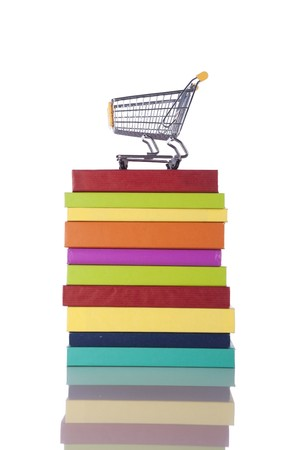 Stack of color books and a shopping cart (isolated on white) photo