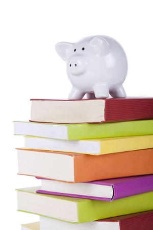 piggy bank over a stack of colorful books (isolated on white) photo