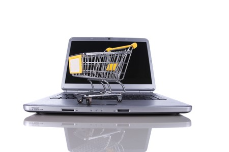 shopping-cart over a laptop isolated on white with reflection Stock Photo - 8027529