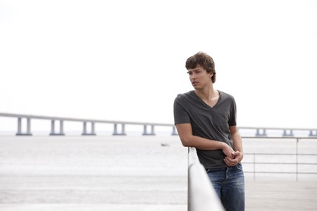only one teenage boy: handsome teenager with a sad face next to the river